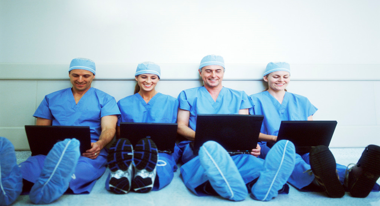 four medical professionals looking at laptops