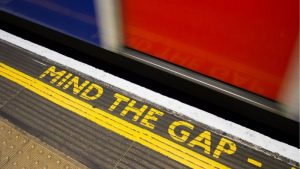 a London underground platform with a train moving and the words Mind The Gap painted on the platform