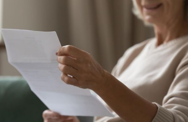 older woman customer reading a printed statement