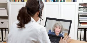 a woman doctor speaking with an older female patient via video chat