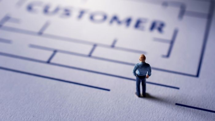 tilt shift style image of a businessman looking at a maze with the word Customer at the center, suggesting a banking customer journey map.