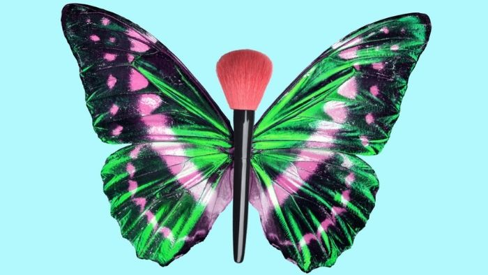 Colorful butterfly with makeup brush as a body on blue background.