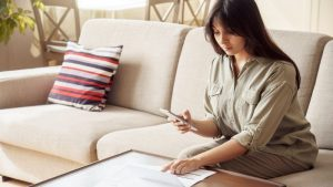 a young woman stilling on a couch looking at a bank statement and her mobile phone
