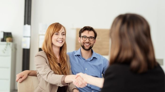 happy couple shaking hands with a credit union loan officer