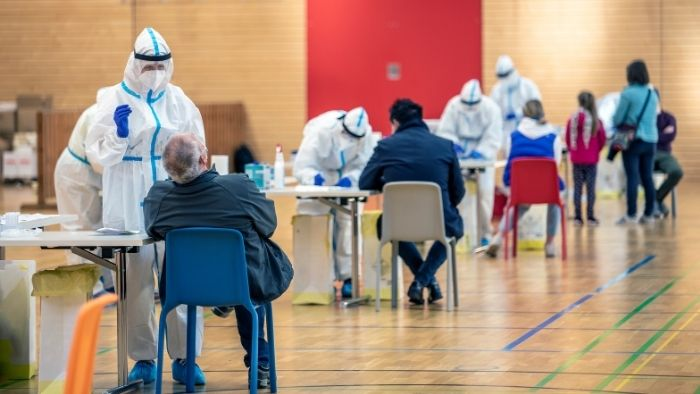 a school gym has been transformed into a Covid testing center with medical workers taking samples from the public