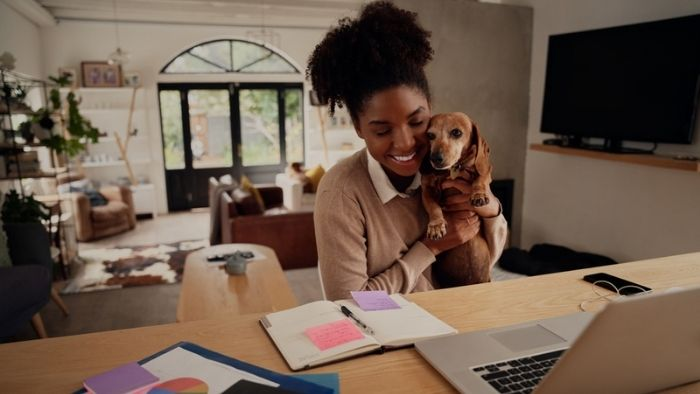 a young woman at her desk and holding her dog, enjoying working from home