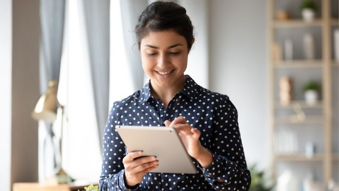 happy young woman reading communication on a tablet