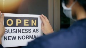 working posting an open for business sign; the new normal for business post-pandemic
