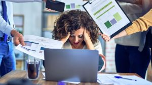 executive woman at laptop stressed by multiple technology issues