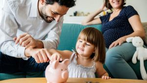 family who are credit union members saving coins in a piggy bank