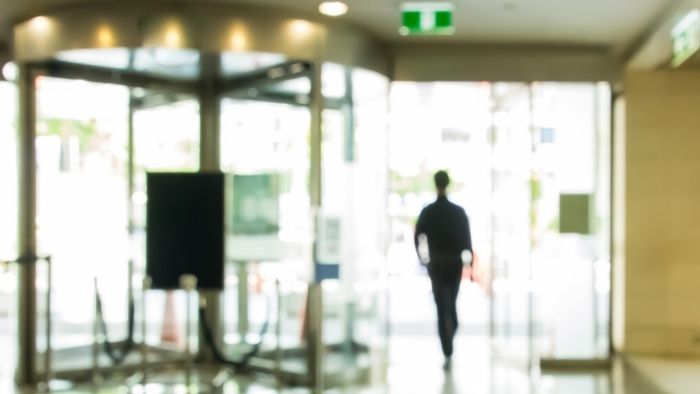 blurred image of a credit union member leaving the branch
