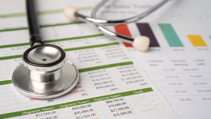 a stethoscope atop medical bills.